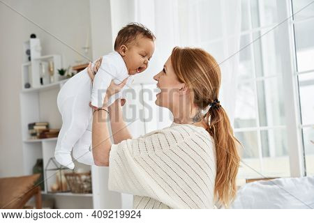 Happy Young Caucasian Mother Lifting Cute Little Baby Daughter. Mum Playing With African American In