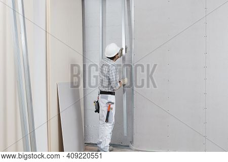 Man Worker With Drywall Metal Profiles For Installing Plasterboard Sheet To Wall. Wearing White Hard
