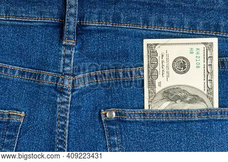 One Hundred Dollar Note In The Back Pocket Of Blue Jeans. Dollar Bills In Jeans Pocket