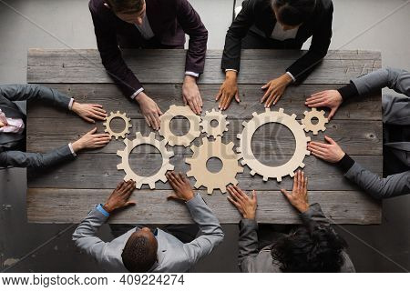 Business People Connect Golden Gear Together At Meeting Table, Success Cooperation Teamwork Concept