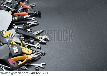 Handyman Tool Kit On Black Wooden Table. Many Wrenches And Screwdrivers, Pilers And Other Tools For