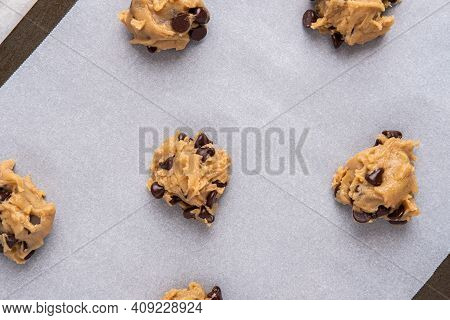 Chocolate Chip Cookie Batter Dollops On A Cookie Sheet With Parchment Paper, Ready For The Oven