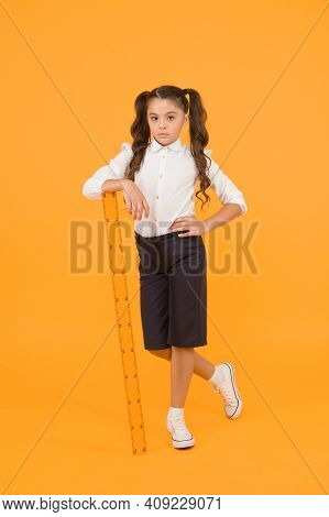 Exploring Stem. Education And School Concept. Sizing And Measuring. Pupil Cute Girl With Big Ruler.