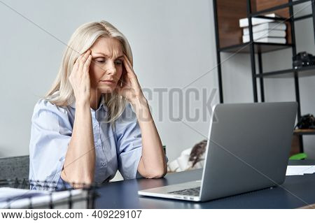 Stressed Forgetful Old Middle Aged Business Woman Suffering From Headache After Computer Work. Tired