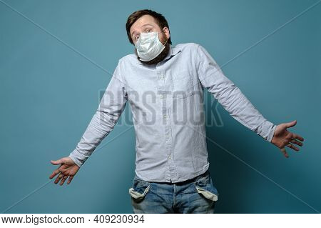 Perplexity Man In A Medical Mask With Empty Pockets And A Questioning Look. No Money. Concept Of Eco