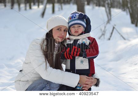 Young Mother Hugging Baby On A Winter Walk In The Park
