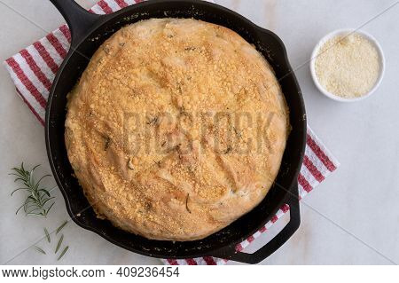 Just Out Of The Oven, No Knead Rosemary Parmesan Skillet Bread, On A Kitchen Towel, With Fresh Rosem