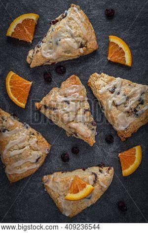 Glazed Cranberry Orange Scones On A Slate Countertop With Dried Cranberries And Orange Wedges