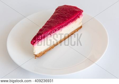 Close Up Of Cheesecake Slice On A White Plate. Raspberry Cheesecake. Copy Space. Selective Focus