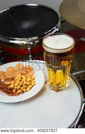 Glass Of Light Beer With Salty Snacks On Professional Drum Set Closeup. Drumsticks, Drums And Cymbal