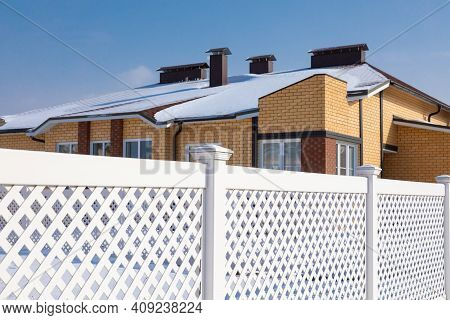 White Plastic Fence In A Modern Cottage Village On A Clear Winter Day. Snow Drifts In Front Of The V