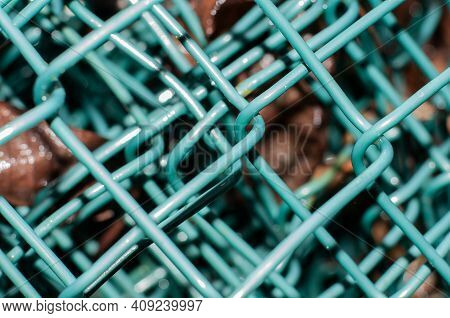 Close Up Of A Chain Link Fence Rolled Up With Wires Covered With Green Plastic