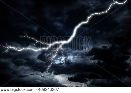 Lightning Strike Against The Background Of A Cloudy Dark Sky.