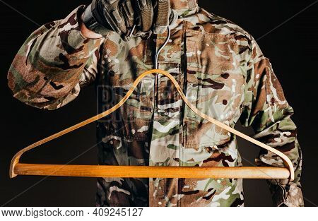 Photo Of Soldier In Camouflaged Uniform And Tactical Gloves Holding Wooden Shirt Hanger On Black Bac