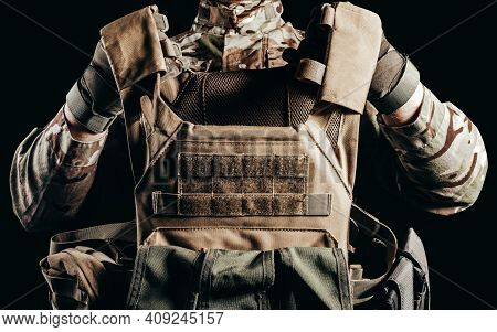 Photo Of Soldier In Camouflaged Uniform And Tactical Gloves Holding Military Armored Vest On Black B