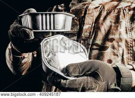 Photo Of Soldier In Camouflaged Uniform And Tactical Gloves Holding Canned Food Field Ration On Blac