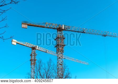 Two Construction Cranes Against The Blue Sky. Many High Tower Cranes Work On The Construction Of New