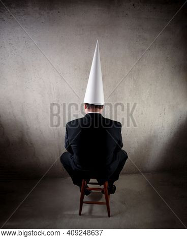 Business man wearing a dunce cap
