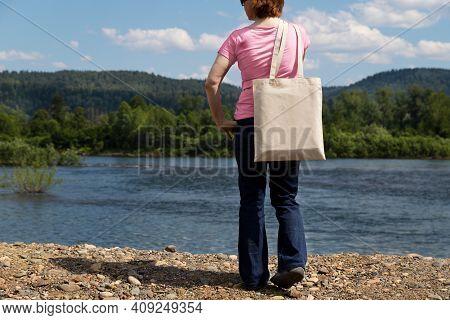 Woman Holding Tote Bag Mockup, River Bank