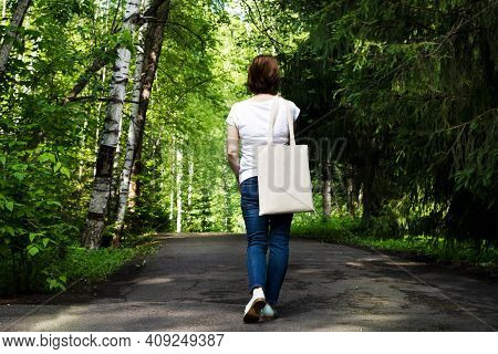 Woman In The Park Holding Tote Bag Mockup