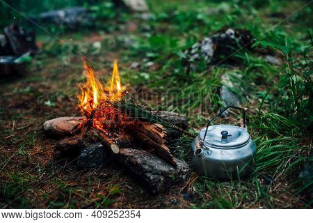 Camping Kettle Near Small Camp Fire Close-up. Cozy Camping Place In Wild. Wonderful Evening Atmosphe