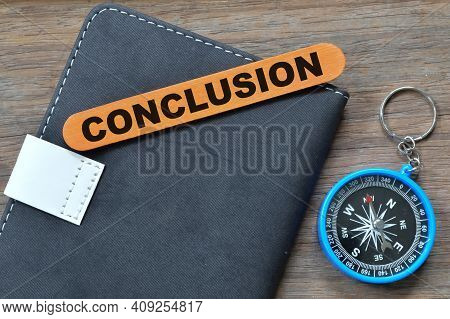 Top View Of Compass, Notebook And Ice Cream Stick Written With Conclusion.