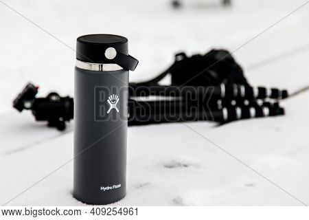NORWALK, CT, USA  -FEBRUARY 9, 2021: Illustrative images from  Hydro flask thermos on snow outside in winter with photographer equipment