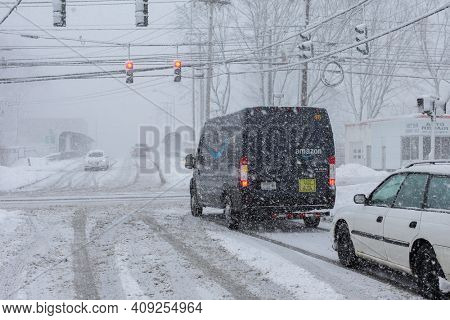 NORWALK, CT, USA -FEBRUARY 7, 2021:  Amazon van on delivering van during snow storm  day on North Taylor Avein Norwalk