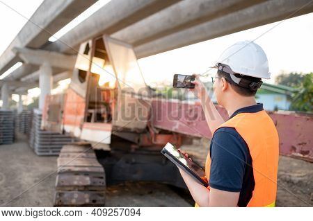 Smart Asian Worker Man Or Male Civil Engineer With Protective Safety Helmet And Reflective Vest Hold