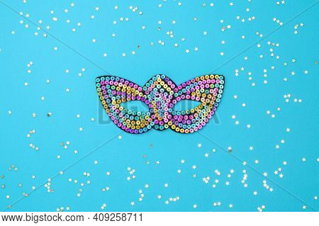 Multicolored Theatrical Mask On A Blue Background. The Concept Of The Venetian Carnival, Celebration