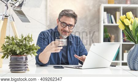 Bearded man shopping online with laptop computer and bank card. Sitting at desk ordering from webshop, paying. Portrait of mature age, middle age, mid adult man in 50s.