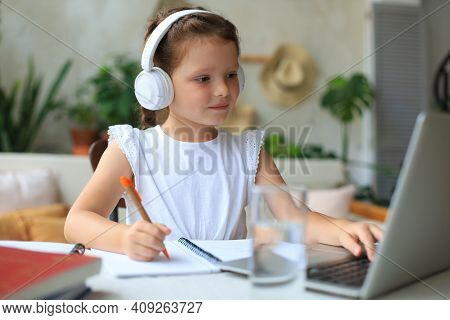 Smiling Little Girl In Headphones Handwrite Study Online Using Laptop At Home, Cute Happy Small Chil