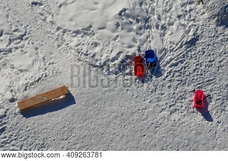 View Of A Snowy Plain With Wooden Park Benches And Several Sleighs And Plastic Children\'s Bobbing T