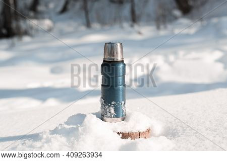 Metal Blue Thermos Standing On A Snowy Tree Stump In A Winter Forest On A Sunny Day