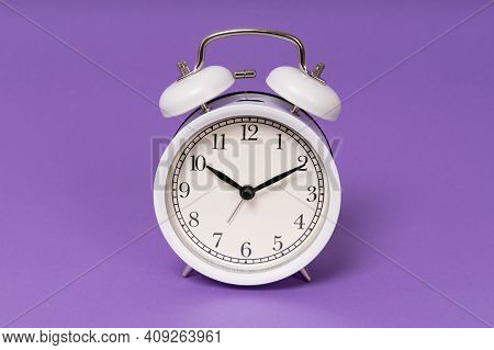 Retro Alarm Clock On Purple Background. Old Fashioned Alarm Clock