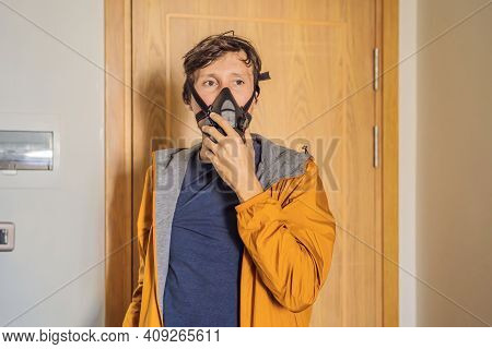 Close Up Portrait Of Young Man Puts On A Respirator Before Leaving The House. Man Puts On A Respirat
