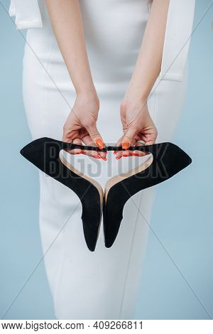 Female Hands Holding Balck High-heel Shoes Over White Dress. Cropped, No Face.