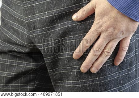 Hand Adult Man In Gray Plaid Trousers And Blue Shirt Close-up.