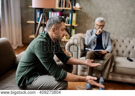 Upset Young Caucasian Man Discussing His Problems With Psychotherapist During Appointment In Office,