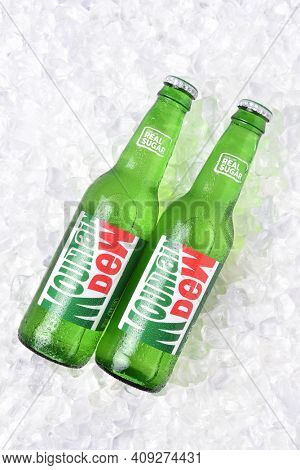 IRVINE, CALIFORNIA - OCTOBER 30, 2017: Two bottles of Mountain Dew soda on ice. Mountain Dew citrus-flavored soft drink by PepsiCo. Mountain Dew was introduced in 1940.