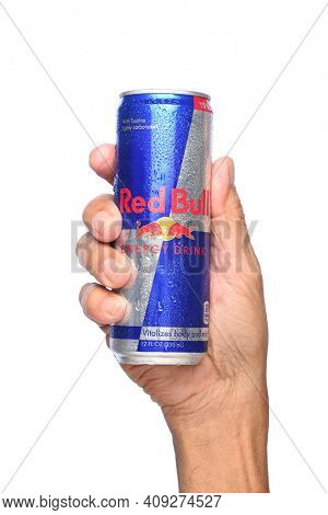 IRVINE, CALIFORNIA - APRIL 26, 2019: Closeup of a hand holding a can of Red Bull Energy Drink. Red Bull is the most popular energy drink in the world.
