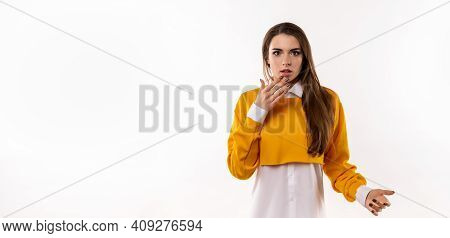 Worried And Concerned Brunette Girl In Casual Clothes Cover Opened Mouth Palm And Looking With Frigh