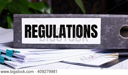 The Word Regulations Is Written On A Gray File Folder Next To Documents. Business Concept
