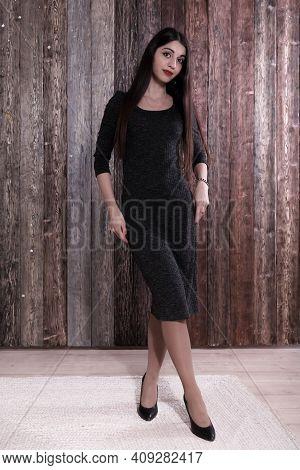 Beautiful Elegant Middle Eastern Woman In A Tight Dark Dress Posing On Wooden Wall Background. Prett