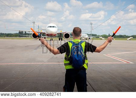 Aviation Marshaller Meets Airplane At The Airport. Airport Worker. Modern Airport. Aviation Business
