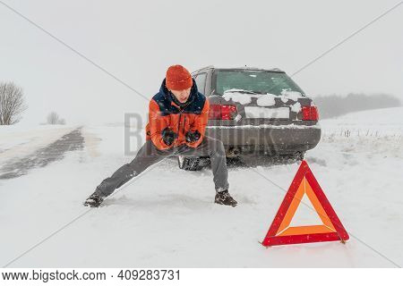 Man In An Orange Jacket Shouts, Jumps, And Gets Angry Near A Triangle Warning Sign Against The Backg