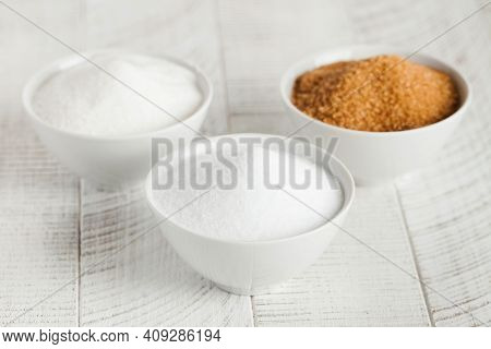 White Sugar, Cane Sugar And Sugar Substitute In Bowls On A Wooden Background.