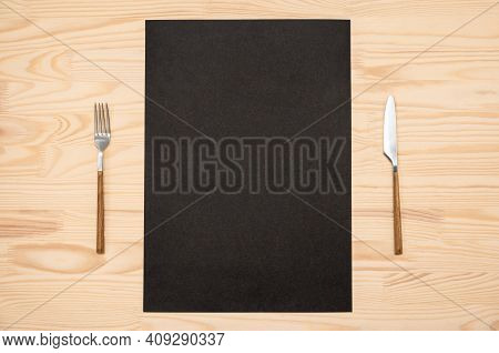 Mockup Blank Black Card A4, A3 And Cutlery On Wooden Table. Top View Black Recipe Paper Page With Mo