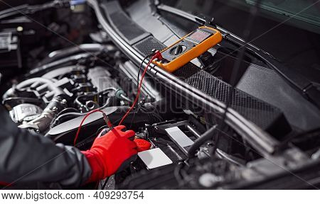 Crop Anonymous Technician In Protective Gloves Measuring Voltage Of Automobile Battery With Voltmete