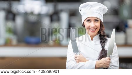 Good-looking Female Chef Stands In The Kitchen Holding Two Knives Smiling At The Camera.